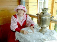 Золотое кольцо России. Мышкин. The Russian woman in traditional clothes of the 19th century drinks tea from a samovar in village Myshkin. Фото Alenmax-Deposit
