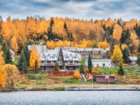 Золотое кольцо России. Плес. Hotel Villa Fortecia in the city of Ples among red autumn trees. View from the water of the Volga. Фото yulenochekk - Depositphotos