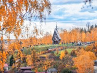 Плес. Wooden Church of the Resurrection on Mount Levitan in the city of Plyos and red autumn trees and roofs of houses. Фото yulenochekk - Depositphotos