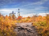 Золотое кольцо России. Плес. Domes and crosses of the Holy Trinity Church in Plyos and red autumn trees and grass. Фото yulenochekk - Depositphotos