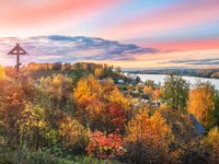 Золотое кольцо России. Плес. Wooden cross on Mount Levitan in Plyos and a view of the Volga against a pink sunset autumn sky. Фото yulenochekk - Depositphotos