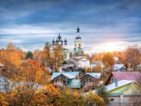 Золотое кольцо России. Плес. Domes and crosses of the Holy Trinity Church in Plyos, houses and red autumn trees and grass. Фото yulenochekk - Depositphotos