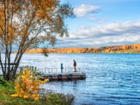 Золотое кольцо России. Плес. Dad and son on a pier on the Volga River in the city of Ples in an autumn sunny day. Фото yulenochekk - Depositphotos