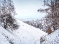 Золотое кольцо России. Плес. View of the town of Plyos in a white haze of snow between the winter hills. Фото yulenochekk - Depositphotos