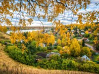 Золотое кольцо России. Плес. Autumn city of Plyos from the height of the Cathedral Mountain through the yellow branches of birch. Фото yulenochekk-Deposit