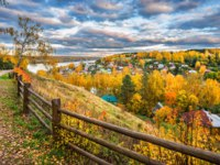 Золотое кольцо России. Плес. Autumn city of Plyos from the height of the Cathedral Mountain behind a wooden fence, small houses and Volga. Фото yulenochekk-Dep