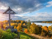 Золотое кольцо России. Плес. Worship Cross on Levitan Mountain in the autumn Plyos on a sunny evening and a view of the Volga. Фото yulenochekk - Depositphotos