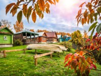 Золотое кольцо России. Плес. Beautiful wooden Russian houses in Plyos and inverted boats in the autumn sunny day. Фото yulenochekk - Depositphotos