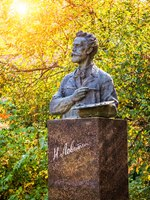 Золотое кольцо России. Плес. Monument to the artist Levitan in Ples next to the autumn golden tree. Фото yulenochekk - Depositphotos