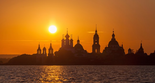 Золотое кольцо России. Ростов Великий. Monastery silhouette against the setting sun at the Lake Nero, Rostov, Russia. Фото bbsferrari - Depositphotos