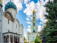 Сергиев Посад. Троице-Сергиева лавра. The bell tower in the Lavra in Sergiev Posad and the dome of the Assumption Cathedral. Фото yulenochekk - Depositphotos