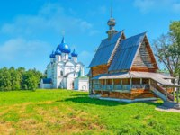 Суздаль. The medieval log St Nicholas church from Glotovo village neighbors with the Nativity Cathedral of Suzdal Kremlin, Russia. Фото efesenko - Depositphotos