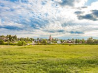 Золотое кольцо России. Суздаль. Rural landscape, field, houses and Church into the distance, Suzdal, Golden Ring, Russia. Фото nymph2201@gmail.com - Depositphotos