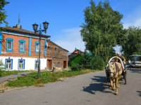 Суздаль. A man driving a horse drawn carriage on the streets of Suzdal in front of the old wooden house on a summer afternoon. Suzdal, Golden Ring, Russia. Фото Balakate-Deposit