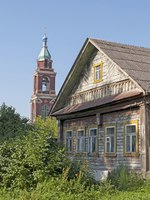 Золотое кольцо России. Юрьев-Польский. Old wooden house on a background of the bell tower, sunny summer morning. Фото viknik - Depositphotos