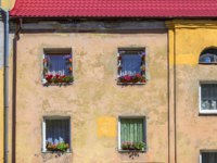 Россия. Архитектура Калининграда. Windows with flowers on the facade of the old house. Kaliningrad, Russia. Фото Belikart - Depositphotos