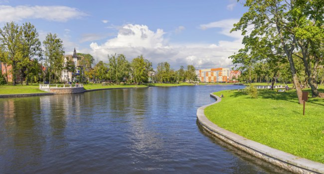 Россия. Калининград. Верхнее озеро. The embankment of the Upper Pond in summer sunny day. Kaliningrad, Russia. Фото Belikart - Depositphotos