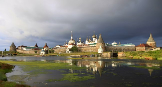 Клуб Павла Аксенова. Россия. Соловецкие острова. Solovetsky monastery against a dark stormy sky illuminated by the setting sun. Фото Galene-Depositphotos