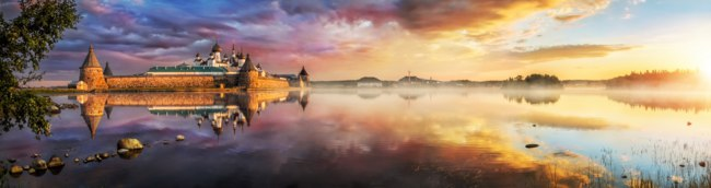 Россия. Соловецкие острова. Morning landscape at the Holy Lake at Solovetsky monastery with dark blue clouds and sun. Фото yulenochekk-Depositphotos