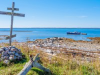 Россия. Соловецкие острова. Wooden cross on the shore of the White Sea and a ship at Anzersky Island. Solovky Islands, Russia. Фото Byelikova-Depositphotos