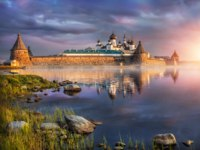 Россия. Соловецкие острова. Summer clouds over the Solovetsky monastery on a summer morning, and the sun rises. Фото yulenochekk-Depositphotos
