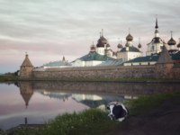 Клуб Павла Аксенова. Россия. Соловецкие острова. Solovetsky monastery at sunrise, in the foreground on the grass is a cow. Фото Lenorlux-Depositphotos