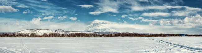 Россия. Камчатка. Panorama of Koryaksky volcano and surrounding snow-covered countryside. Kamchatka, Russia. Фото amoklv - Depositphotos