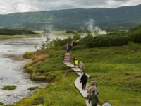 Россия. Камчатка. Tourists walk on a wooden path in the Uzon Caldera. Kronotsky Nature Reserve on Kamchatka Peninsula. Фото yykkaa -Depositphotos