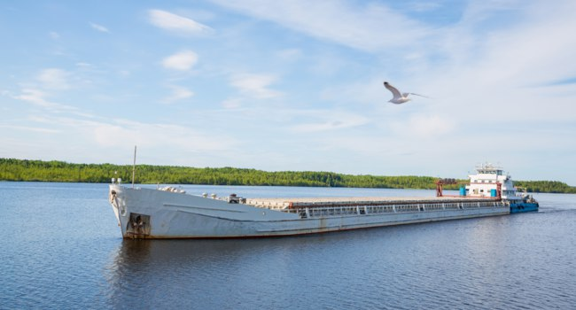 Россия. Карелия. Ладожское озеро. Cargo ship goes on the river Svir River. Karelia, Russia. Фото Stas_K - Depositphotos