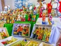 The handmade and painted wooden Christmas toys in historic dress in the stall of Izmailovsky market, Moscow, Russia. Фото efesenko-Depositphotos