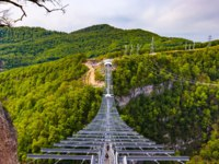 Россия. Сочи. Курорт Красная поляна. A metal pedestrian suspension bridge across the Mzymta River canyon. Фото ValeryBocman - Depositphotos
