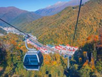 Сочи. Курорт Красная поляна. Cableway with ski lifts and cabins for tourists, town and the autumn forest in the mountains of the Caucasus. Фото aapsky - Depositphotos