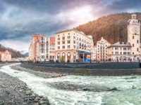 Сочи. Красная поляна. Курорт Роза Хутор. Mzymtu River, the Town Hall tower of the mountains on Rosa Khutor in Sochi. Фото yulenochekk - Depositphotos