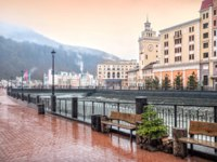 Сочи. Красная поляна. Курорт Роза Хутор. View of shops, cafes, the river and the snowy peaks of the mountains on Rosa Khutor in Sochi. Фото yulenochekk-Depositph