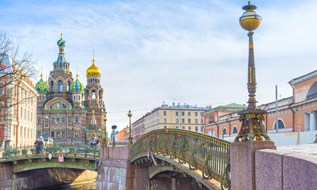 The scenic old fashioned streetlight on Malokonushenny bridge with the Church on Spilled Blood on the background in Saint Petersburg. Russia. Фото efesenko-Depos