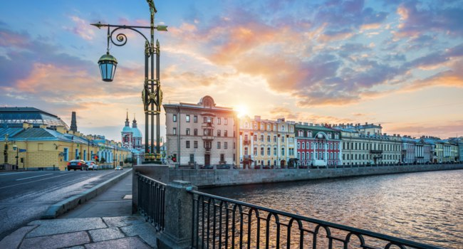 Panteleymonovsky bridge with a lantern across the Fontanka river in St. Petersburg and the embankment in the first rays. Фото yulenochekk-Depositphotos