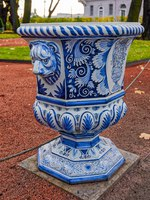 Close-up view of a big street white and blue ceramic flowerpot with lions at the path of Summer Garden in the city center. Фото Igor-SPb - Depositphotos