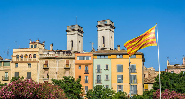 Клуб Павла Аксенова. Испания. Каталония. Жирона. Flag of Catalonia waving in the downtown of Girona. Spain. Фото photooiasson - Depositphotos