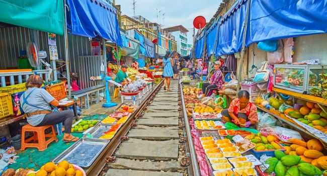 Maeklong Railway Market (Talad Rom Hoop) boasts wide range of fresh fruits, vegetables, local foods, snacks and souvenirs in Maeklong. Фото efesenko - Depositphotos