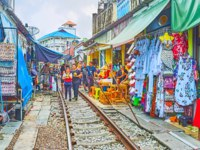 The tourists walk the railroad of Maeklong Railway Market, lined with garment, food and souvenir stalls in Maeklong. Фото efesenko - Depositphotos