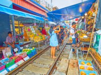 The tourists and visitors walk along the railroad of Maeklong Railway Market, make pictures and choose fresh fruits and other foods in Maeklong. Фото efesenko - Deposit
