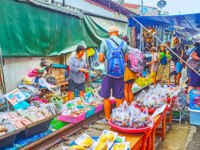 The tourists walk the railroad and make shopping in stalls of Maeklong Railway Market - the popular tourist spot in country in Maeklong. Фото efesenko - Depositphotos