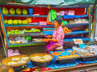 The tiny fruit stall of Maeklong Railway Market offers green papayas, packed pieces of durian, Thai herbs and spices in Maeklong. Фото efesenko - Depositphotos