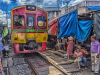 Tourists take photo at the train running through the most popular spot Talad Rom Hup or Umbrella market at Mae Klong railway station. Фото evdoha - Depositphotoss
