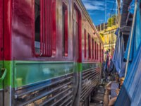 Tourists take photo at the train running through the most popular spot Talad Rom Hup or Umbrella market at Mae Klong railway station. Фото evdoha - Depositphotos