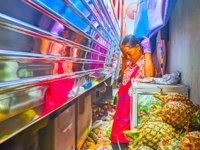 The vendor is leaning against the wall, while the train is riding through the Maeklong Railway Market(Talad Rom Hoop)in Maeklong.Фото efesenko-Deposit