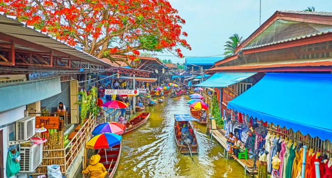 The umbrellas and boats of Damnoen Saduak floating market with narrow khlong and blooming flame tree over the roofs in Damnoen Saduak. Фото efesenko-Deposit