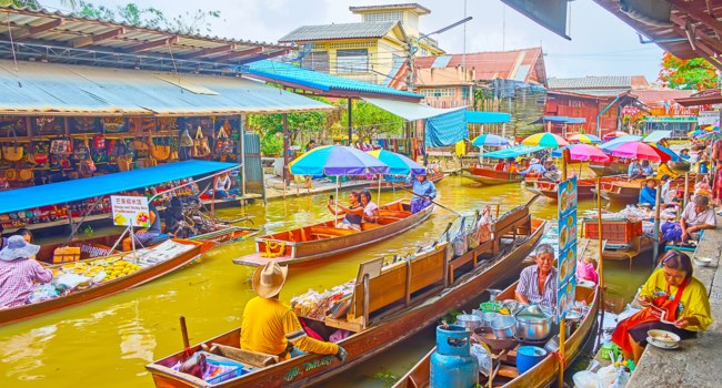 The numerous moored sampan food boats attract tourists to buy the lunch and eat on the bank of Damnoen Saduak floating market. Фото efesenko-Deposit