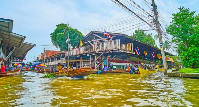 The busy canal junction in Ton Khem floating market, with a view on shabby trade pavilions and fast floating boats in Damnoen Saduak. Фото efesenko - Depositphotos