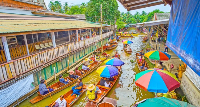 The boat traffic jam on narrow canal of Ton Khem floating market; many kayaks try to enter under the bridge in Damnoen Saduak. Фото efesenko-Deposit